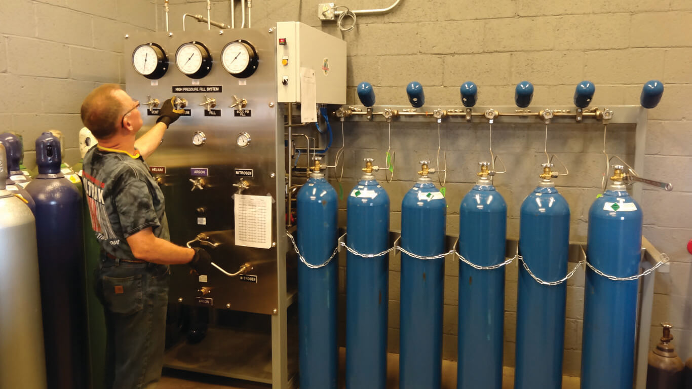 man at a control station filling various gas cylinders