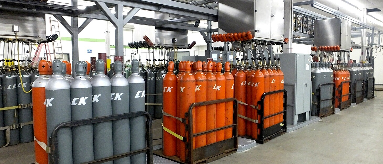 gas cylinders in gas packs being filled by a automated filling station