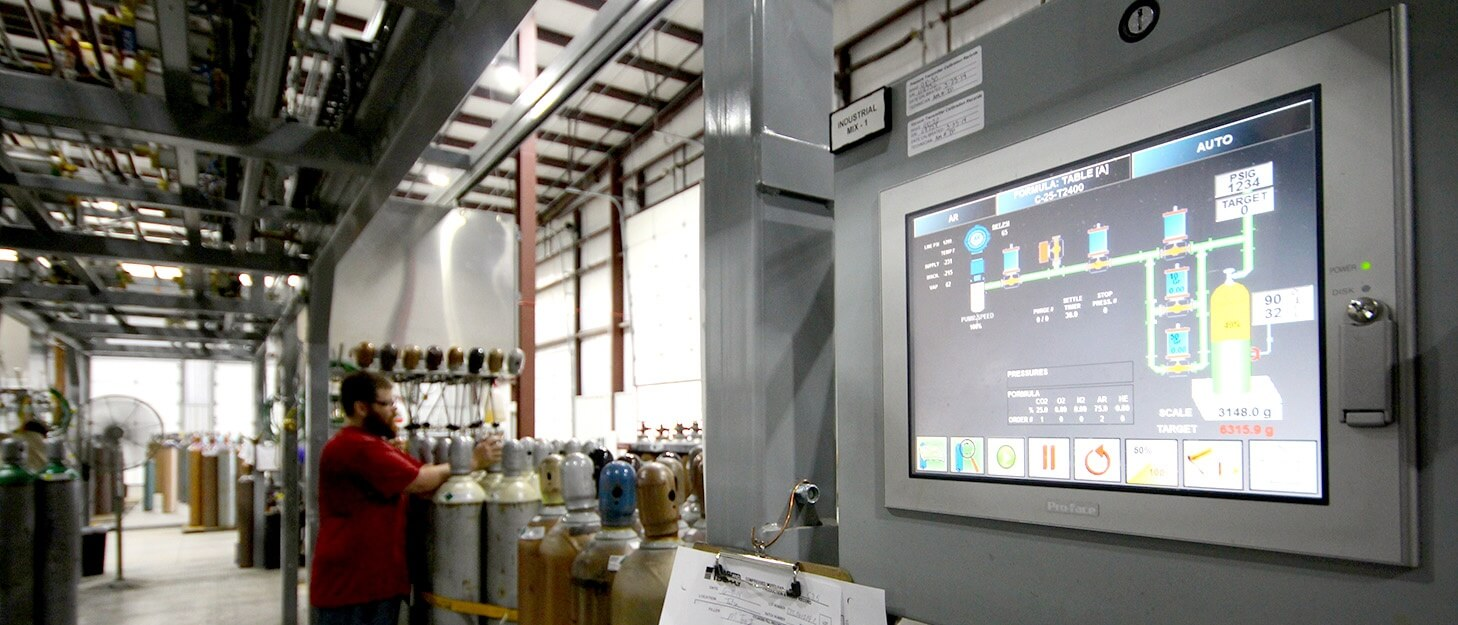 touch screen control panel with man putting protection cap on a gas cylinder in the back ground