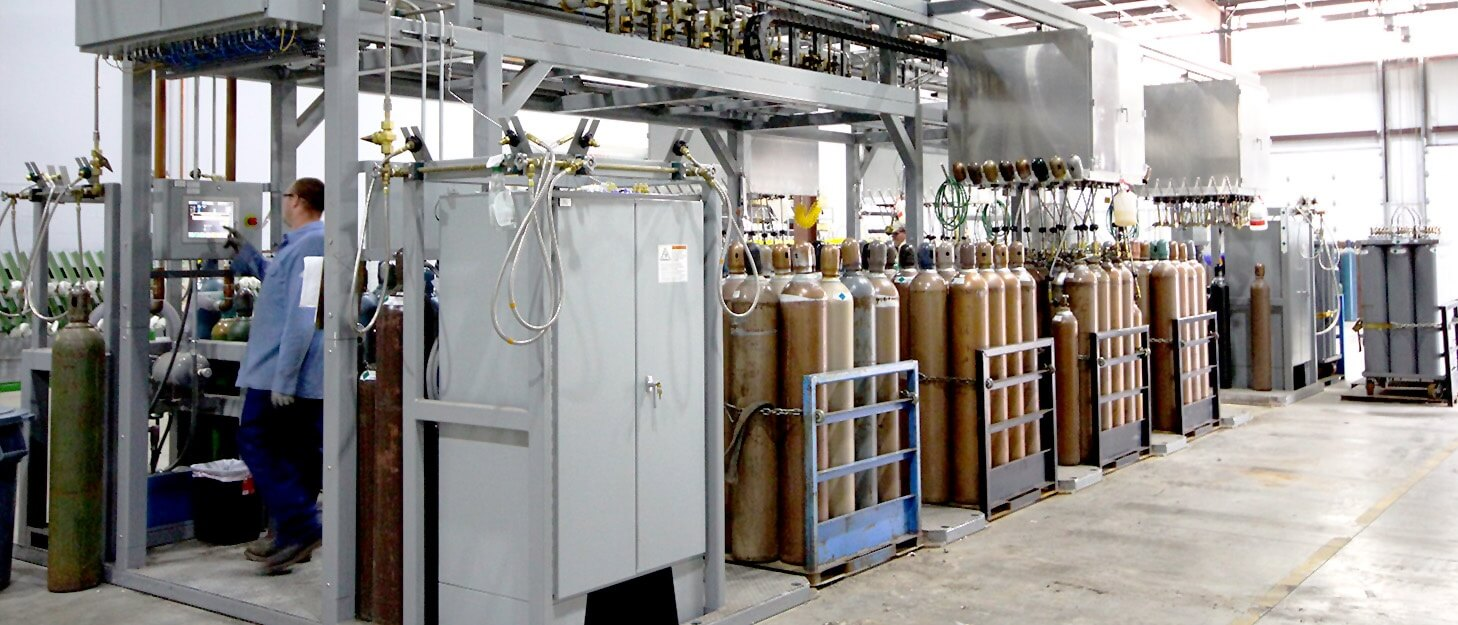 man using a control panel to fill various gas cylinders