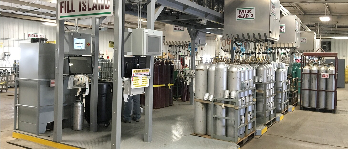 various gas cylinders in gas pallets around automated gas cylinder filling equipment