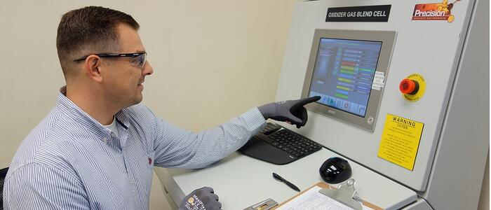 man working at a control panel for a gas cylinder fill system