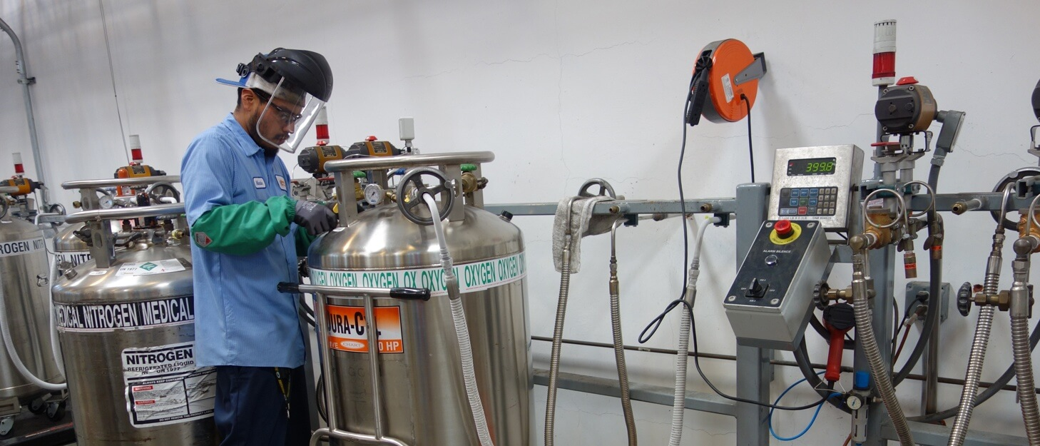 man filling a large gas cylinder with oxygen