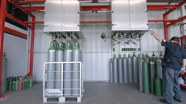 Man filling gas cylinders using a Weldcoa automated industrial fill system