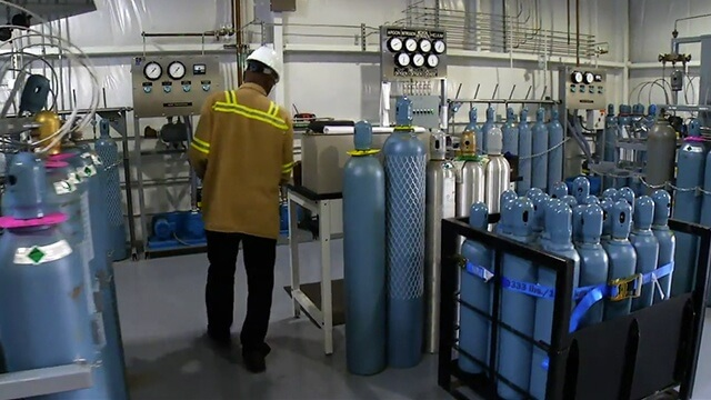 man at Linde's automated filling system featuring various gas cylinders