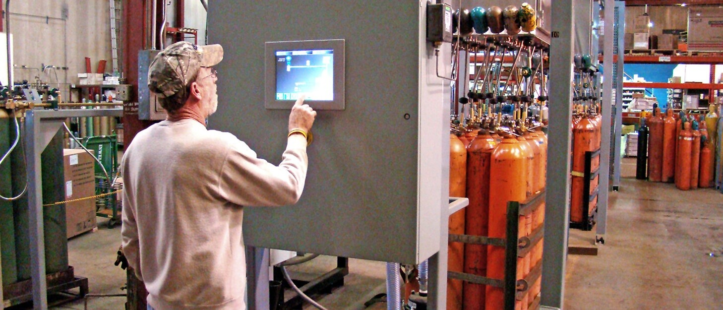 man using a control panel to fill gas cylinders at a American Welding & Gas filling plant