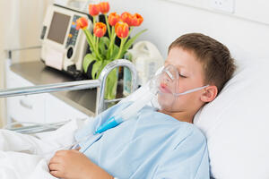 Sick little boy wearing oxygen mask in hospital ward